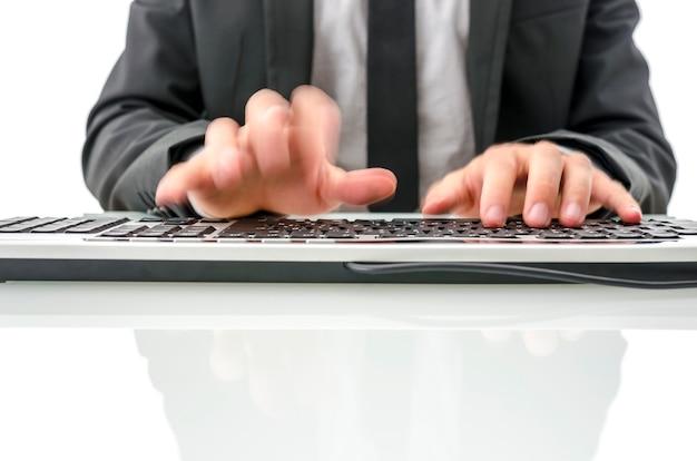 Mains floues d'un homme d'affaires travaillant sur ordinateur.