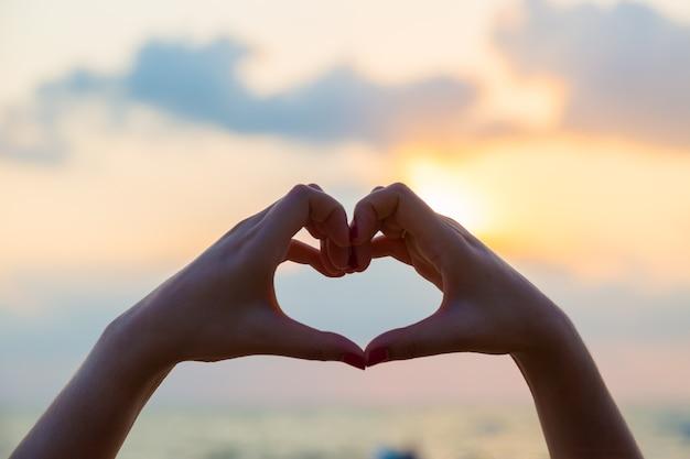 Les mains font en forme de coeur l'amour avec la silhouette au coucher du soleil