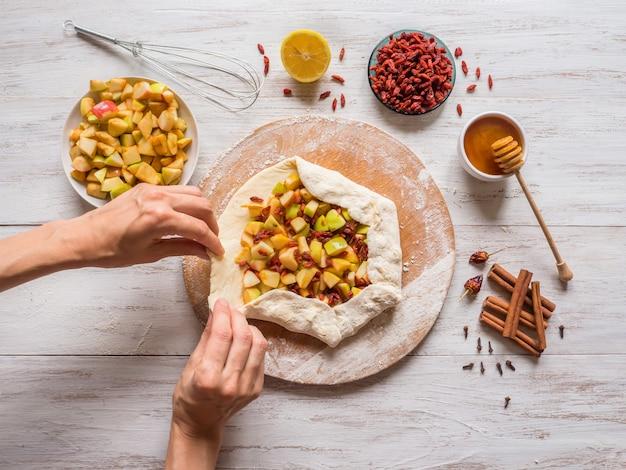 Les mains font de la pâte à tarte aux pommes ou à la baie de goji. tarte aux pommes pour les vacances.