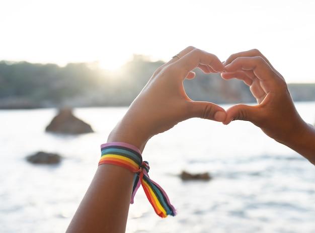Mains formant un coeur sur la plage