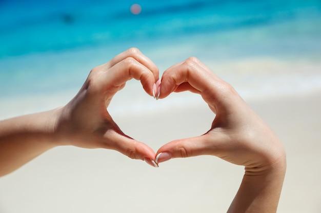 Les mains en forme de coeur. plage tropicale. concept d'amour