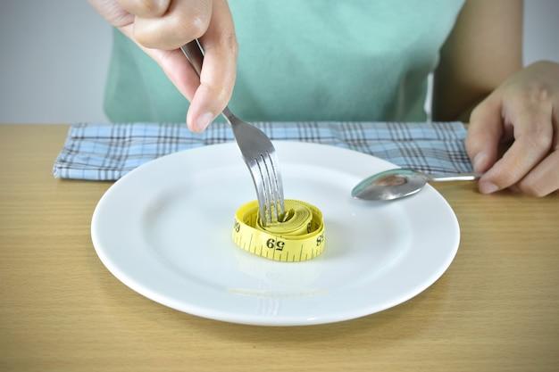 Mains avec fourchette et ruban à mesurer sur plaque.
