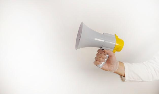 Mains gantées à l'aide d'un mégaphone, avec copie espace