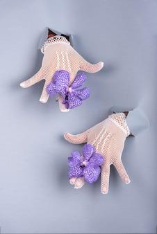 Mains gantées au soleil d'un trou inférieur bleu avec deux orchidées bleues