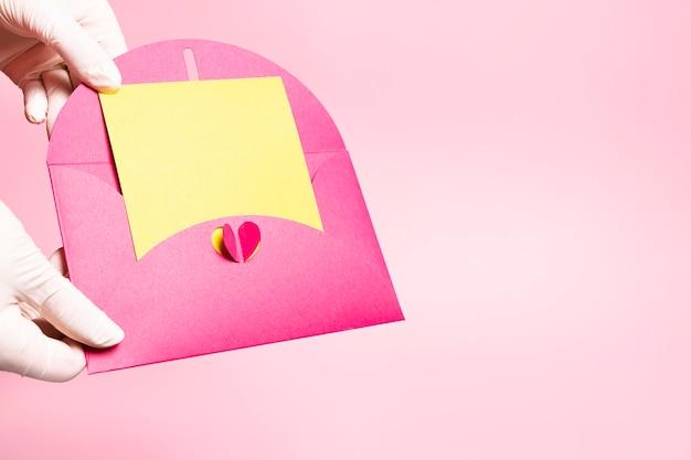 Des mains gantées tiennent une enveloppe romantique ouverte.