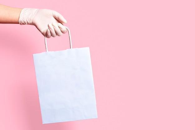 Des mains gantées tiennent un sac en papier.