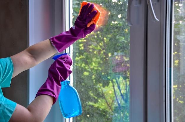 Mains avec des gants en caoutchouc, flacon pulvérisateur avec nettoyant pour vitres pour essuyer le verre sale dans la pièce avec un chiffon.