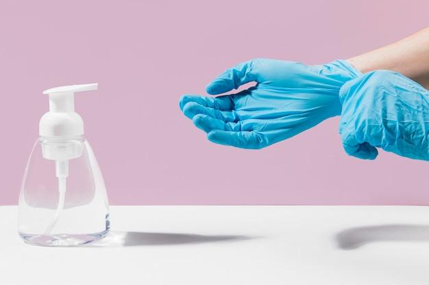 Mains avec des gants chirurgicaux à l'aide d'un désinfectant pour les mains