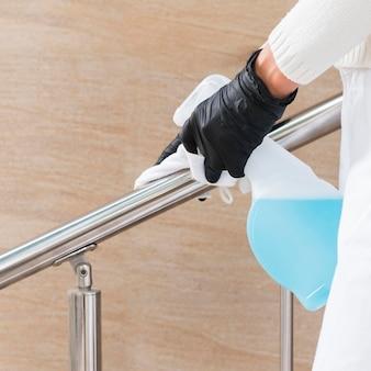 Mains avec des gants désinfectant la main courante