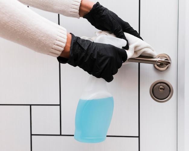 Mains avec des gants de désinfection de la poignée de porte