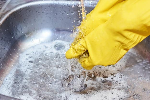 Mains en gants jaunes, évier de nettoyage dans la cuisine