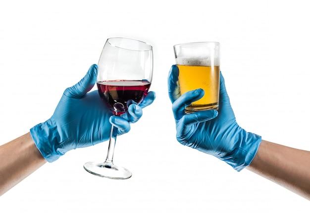 Mains avec des gants en latex bleu grillage avec verre de bière et vin rouge