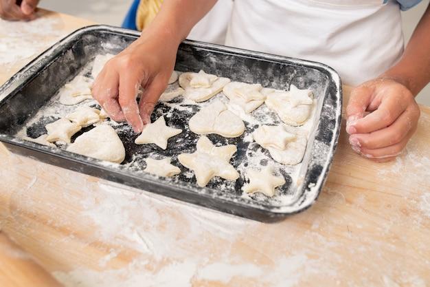 Mains de garçon coupant des biscuits à partir de pâte roulée pendant la cuisson de la pâtisserie pour le dîner de noël