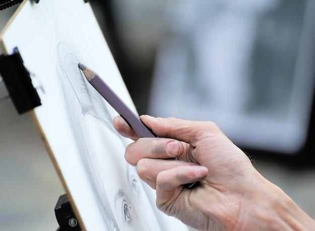 Mains de garçon avec un crayon, dessin sur papier blanc