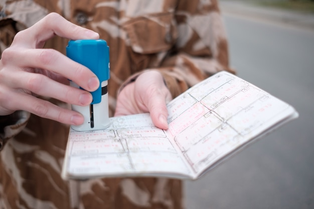 Mains de garde-frontière féminine; tamponner le passeport pendant le contrôle aux frontières