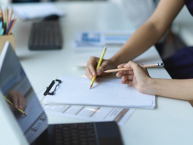 Les mains de gens d'affaires travaillant ensemble sur la paperasse sur le presse-papiers sur la table