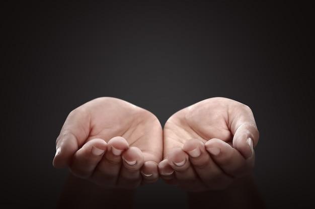 Les mains des gens avec un geste de prière
