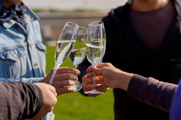 Les mains des gens qui frappent dans des coupes de champagne ou de vin blanc.