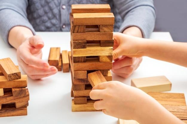 Mains grand-mère et petit-fils jouent au jeu de société avec des blocs de bois