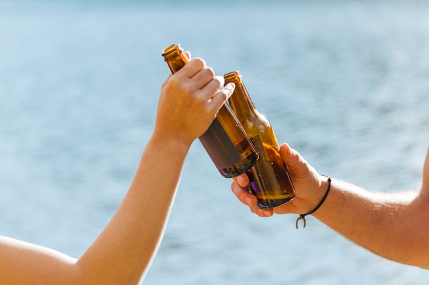 Mains, grillage, bouteilles bière