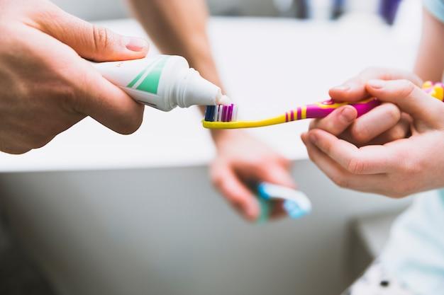 Mains gros plan, mettre, dentifrice, sur, brosse