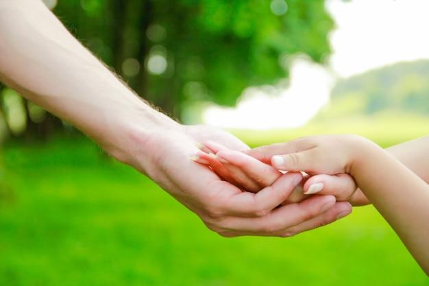 Mains heureux parents et enfant à l'extérieur dans le parc