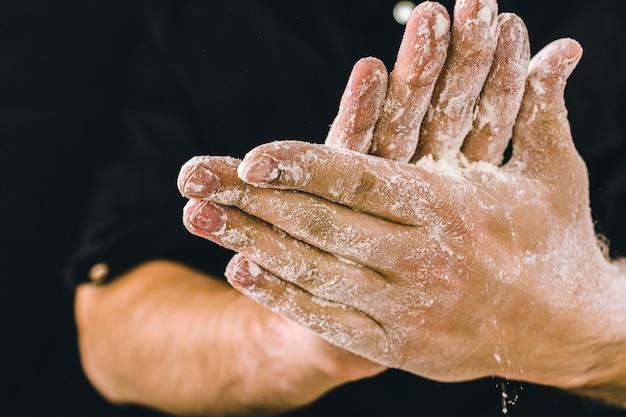 Les mains de l'homme adulte travaillent avec de la farine, photo sombre