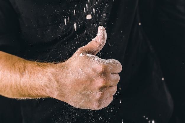 Les mains de l'homme adulte travaillent avec de la farine