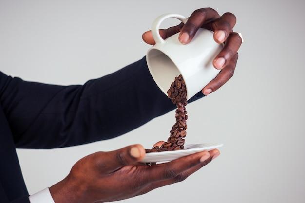 Mains d'homme d'affaires afro-américain dans un costume classique noir tenant une tasse avec des éclaboussures de grains de café volants sur une plaque en arrière-plan blanc tourné en studio. boisson magique du matin