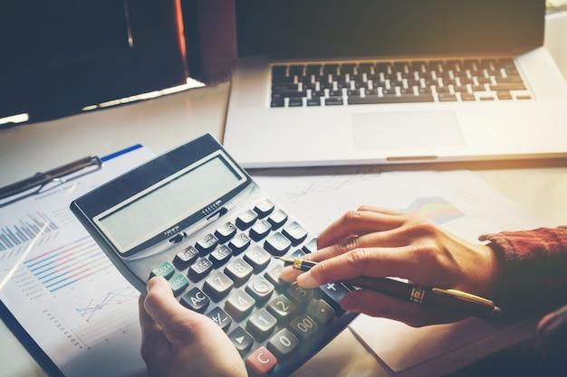 Mains d'homme d'affaires avec calculatrice et utilisant un ordinateur portable au bureau et données financières
