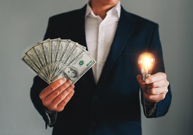 Mains d'homme d'affaires détenant une ampoule lumineuse et des billets en dollars