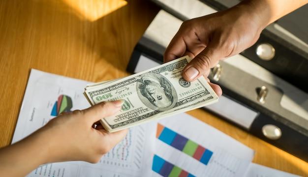 Mains d'homme d'affaires distribuant de l'argent sur une affaire