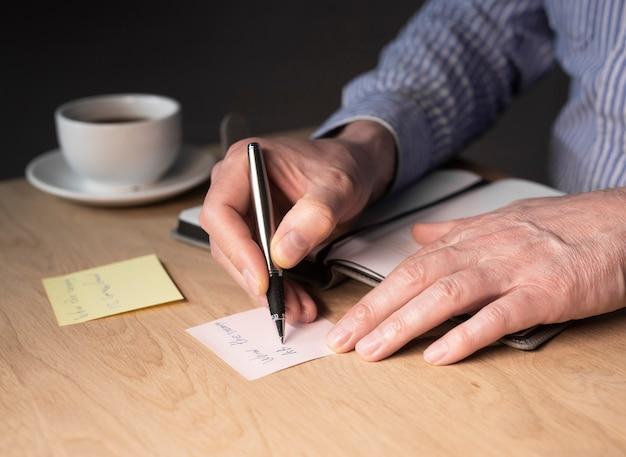 Mains d'homme d'affaires écrivant des notes de mémo ou un rappel sur un autocollant au bureau.