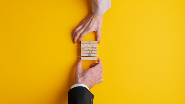 Mains d'un homme d'affaires et femme d'affaires empilant des chevilles en bois pour assembler une image d'ampoule