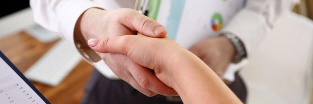 Mains d'homme d'affaires et femme d'affaires partenaires debout dans le bureau et faire un accord par la poignée de main, gros plan.