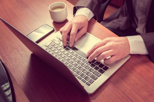 Mains homme d'affaires sur un ordinateur portable