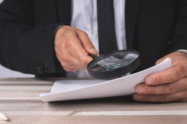 Mains d'un homme d'affaires à la recherche de documents à travers une loupe
