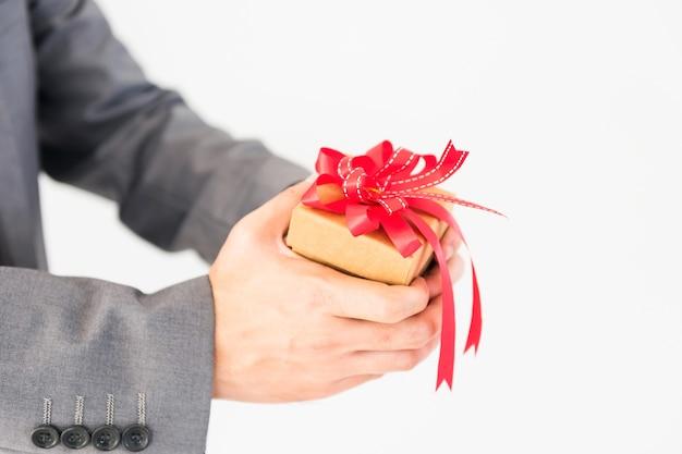 Mains d'homme d'affaires tenant et donnant une boîte-cadeau avec ruban rouge arc