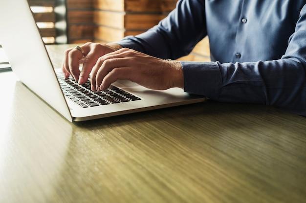 Mains d'un homme d'affaires en train de taper sur un ordinateur portable