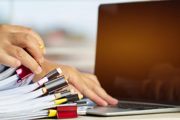 Mains d'homme d'affaires travaillant dans des piles de fichiers papier à la recherche d'informations inachevées