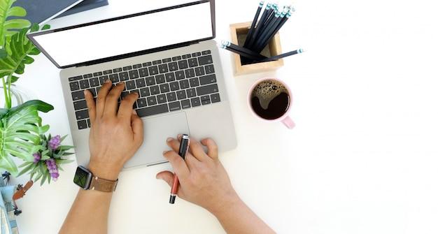 Mains d'homme d'affaires travaillant avec un ordinateur portable à écran blanc