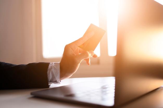Mains d'un homme d'affaires utilisant un ordinateur portable et une carte sur internet
