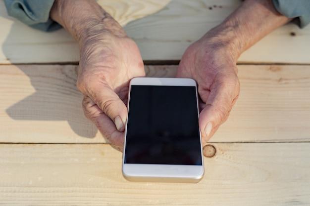Mains d'un homme âgé tenant et utilisant un téléphone. le concept d'enseignement des nouvelles technologies aux personnes âgées, la communication avec la génération plus âgée. image.