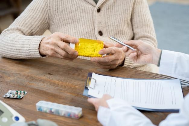 Mains d'un homme âgé en tenue décontractée tenant une bouteille de pilules sur une table alors qu'il était assis devant un médecin lui donnant des recommandations médicales