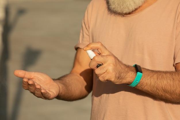 Les mains de l'homme à l'aide d'un distributeur de désinfectant pour les mains, contre le nouveau coronavirus ou la maladie à virus corona covid-19 dans un lieu public. concept antiseptique, hygiène et santé.