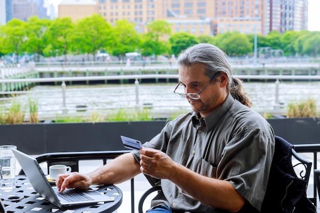 Mains d'homme à l'aide d'un ordinateur portable et détenant une carte de crédit avec des achats en ligne à la lumière du matin
