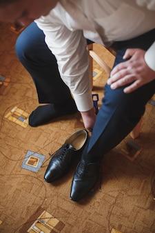 Les mains de l'homme attachant le lacet de ses nouvelles chaussures