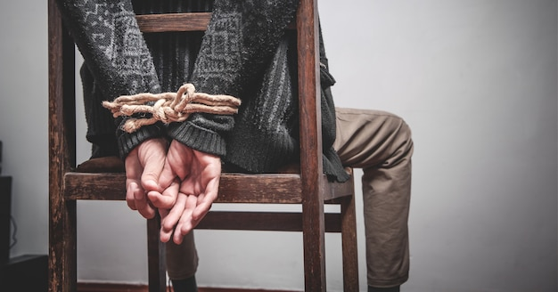 Les mains de l'homme attachées par une corde. emprisonnement