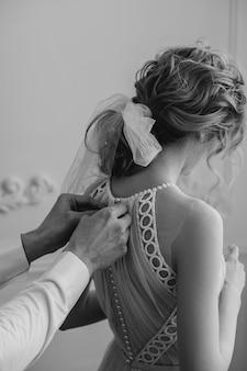 Les mains de l'homme attachent les boutons sur une robe élégante
