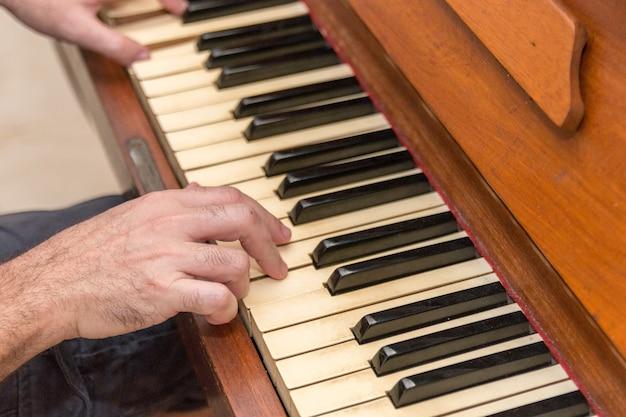 Mains d'un homme blanc jouant du piano à rio de janeiro au brésil.